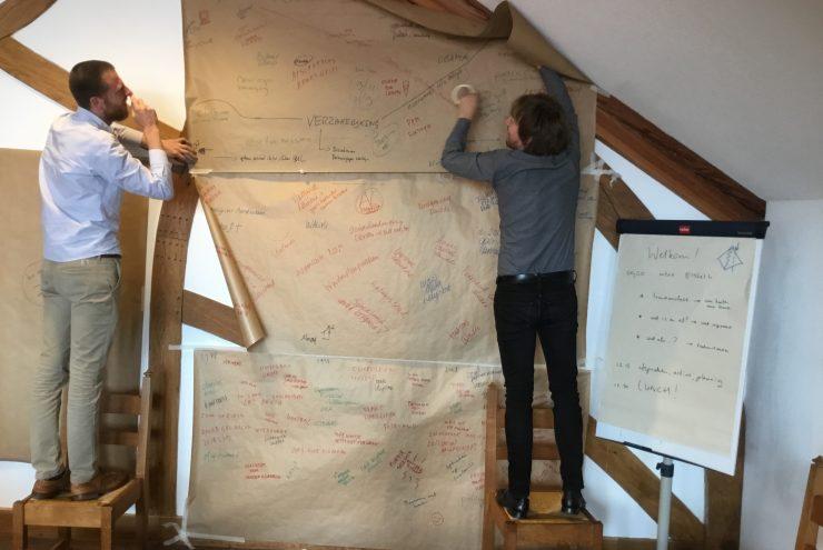 Twee mannen hangen bruine vellen papier met aantekeningen aan de muur