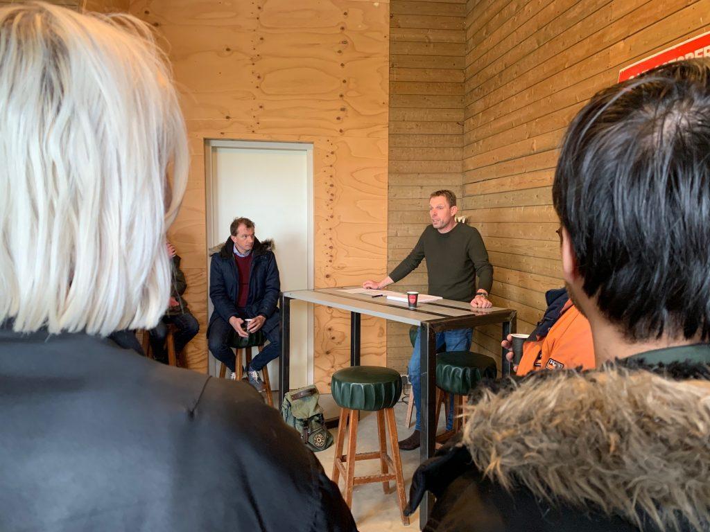Aard, de eigenaar van de Meerhof, spreekt de bezoekers toe van achter een tafel.