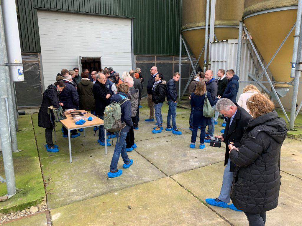 De deelnemers van de expeditie XL dragen blauwe schoenbeschermers en kijken van buiten naar binnen de kippenschuur in.